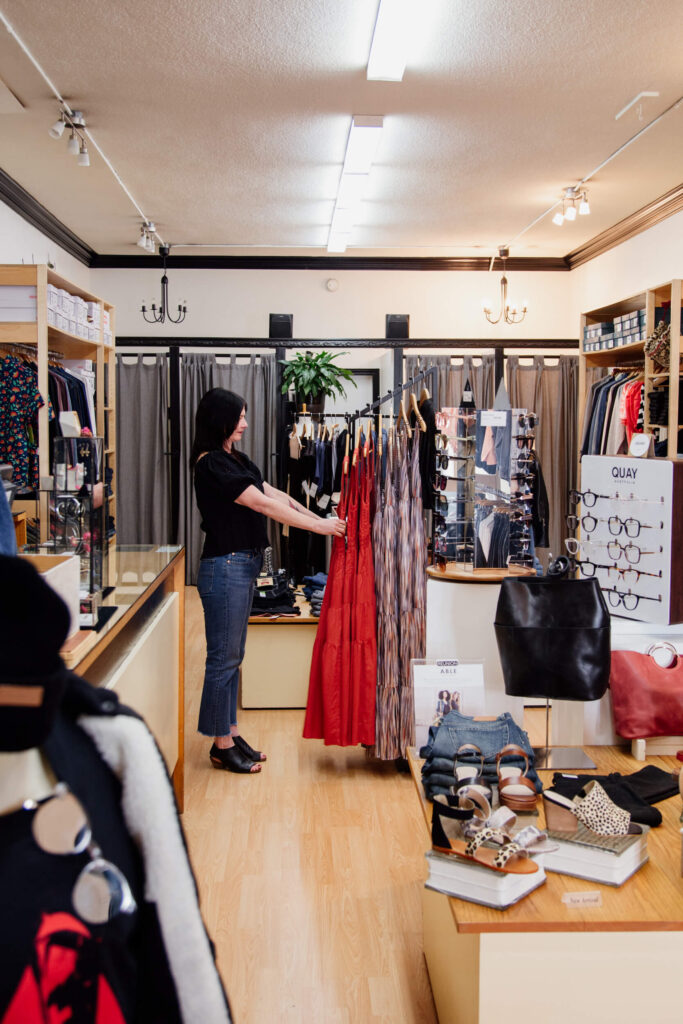 A shop owner fixing a dress on a rack in her store in Victoria, BC.