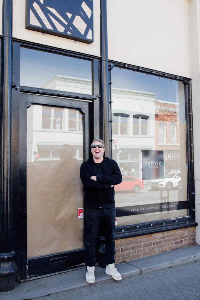 A shop owner laughing in front of his shop in Victoria, Canada.