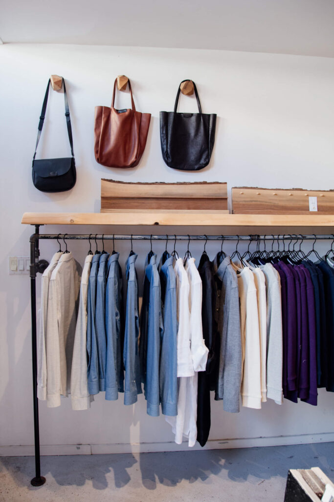 Clothes and bags hanging on a rack in a clothing shop in Victoria, Canada.