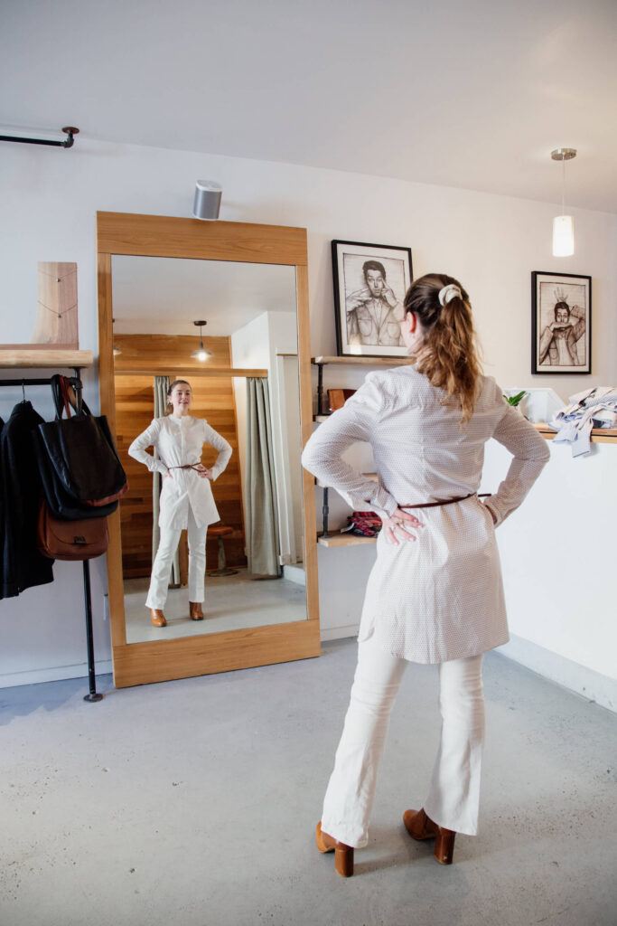 A woman modelling a shirt in front of a mirror in a clothing shop in Victoria, Canada.