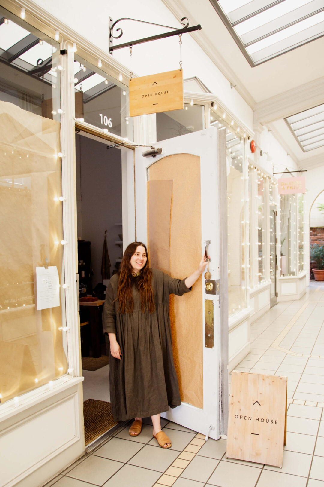 A shopowner stands outside her shop doors.