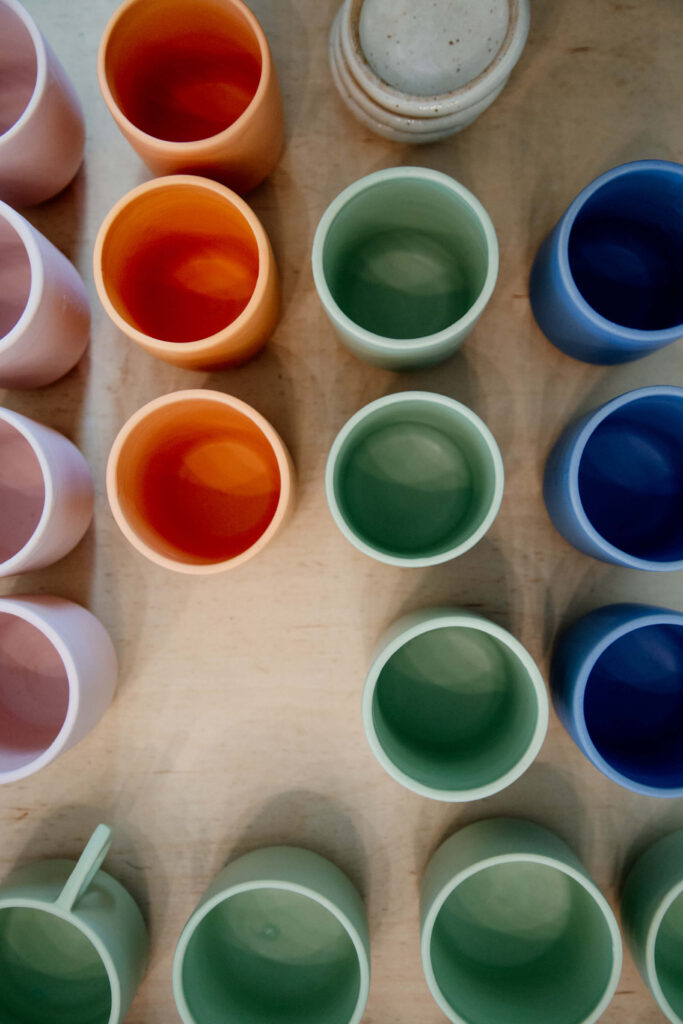 Colourful ceramic mugs on display at a shop.