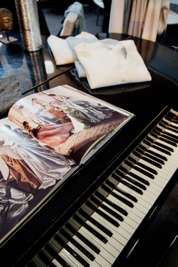 A fashion book opened a top a grand piano.