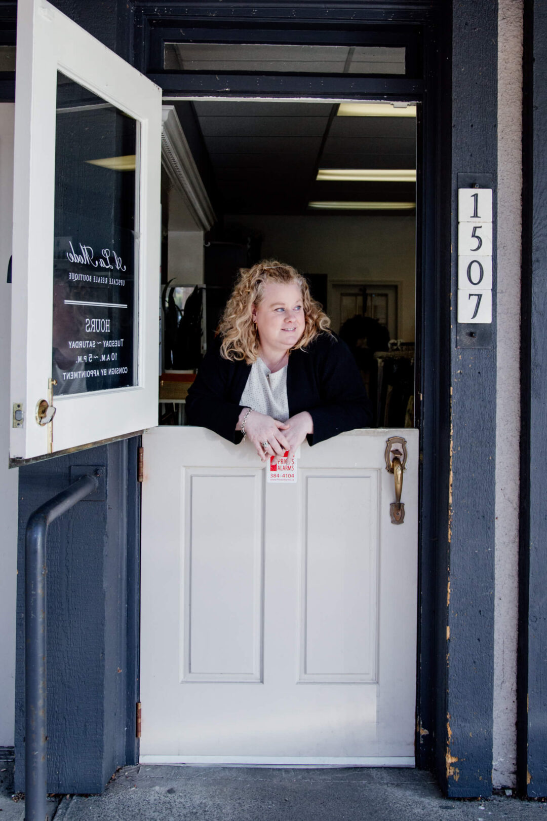 A shopowner leans on the doors at the front of her store.,