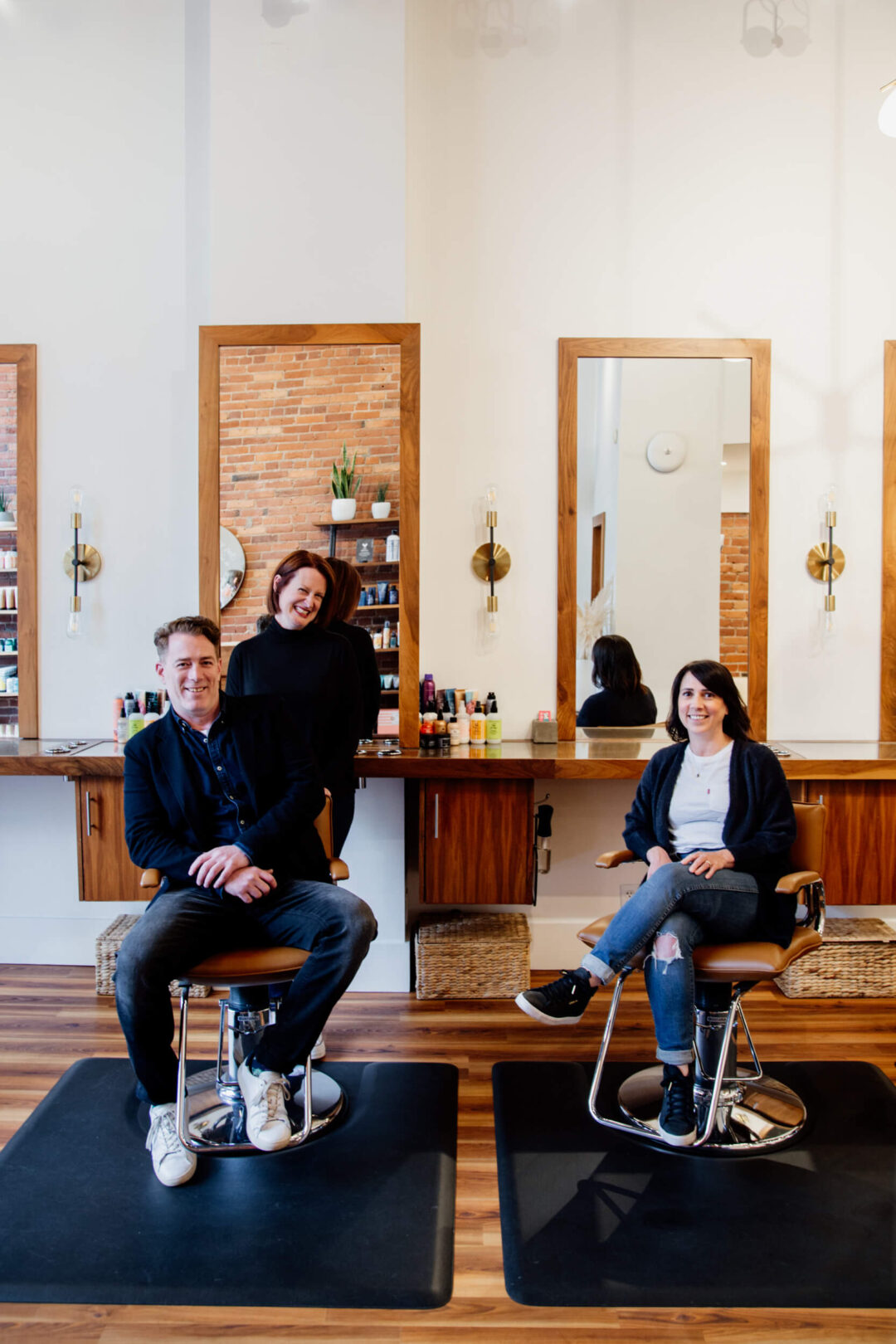 Three salon owners smile at camera while sitting on chairs.