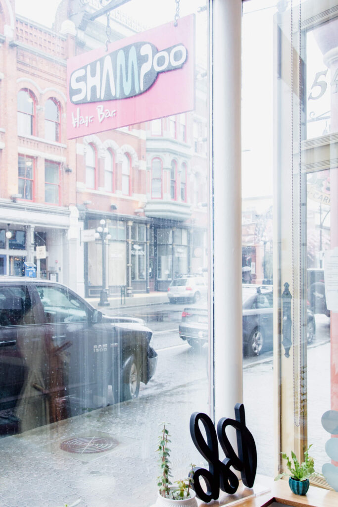The view through salon windows to a rainy street.