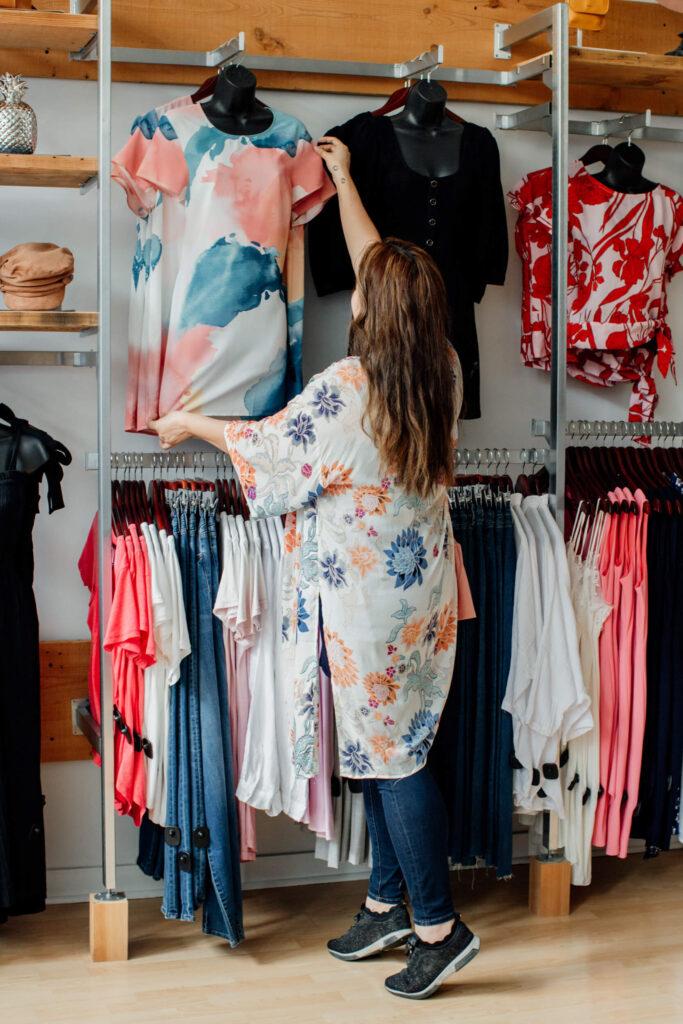 Shopkeeper going through shirts on the racks.