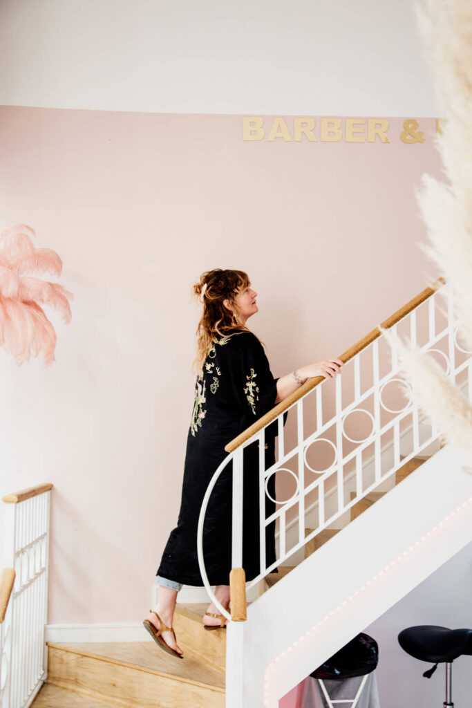 Shop owner going up a staircase in her salon in Victoria, BC.