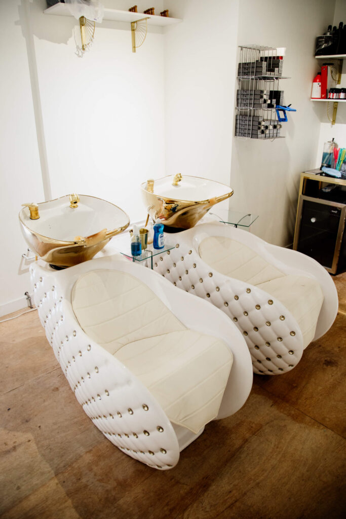 Two white and gold hair washing chairs in a salon.