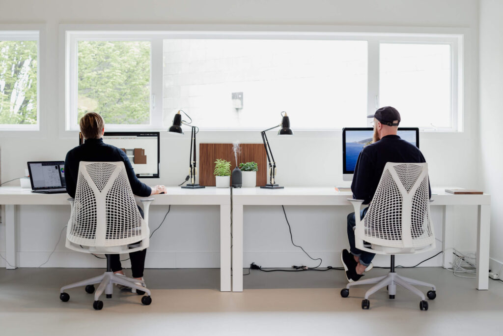 Two designers sit at their desks in an office in Victoria, BC.