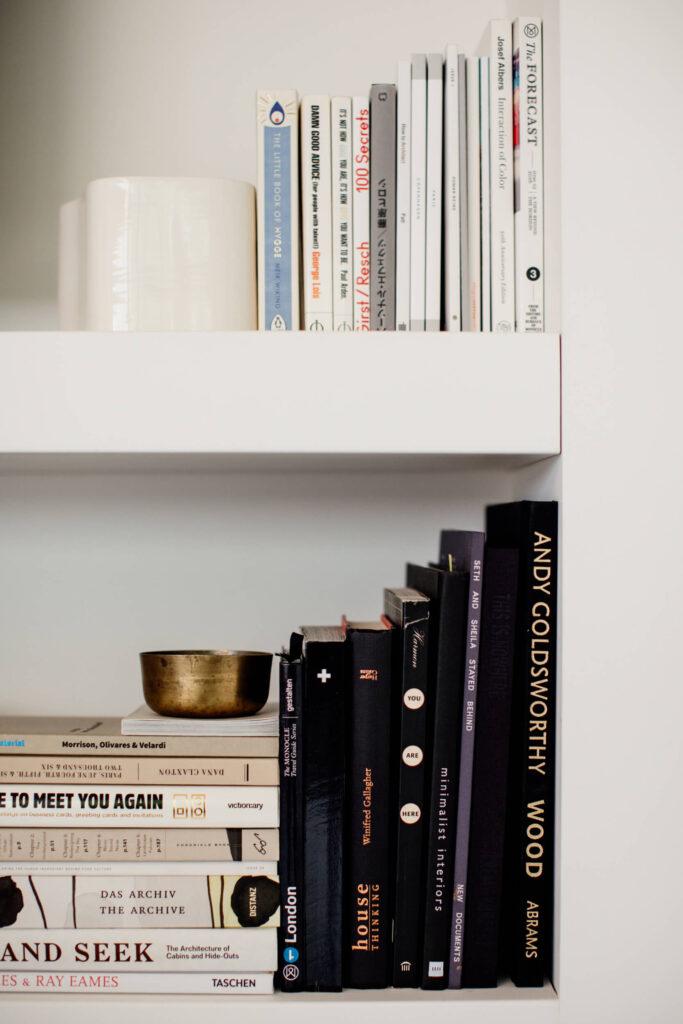 Books on a shelf in studio in Victoria, BC.
