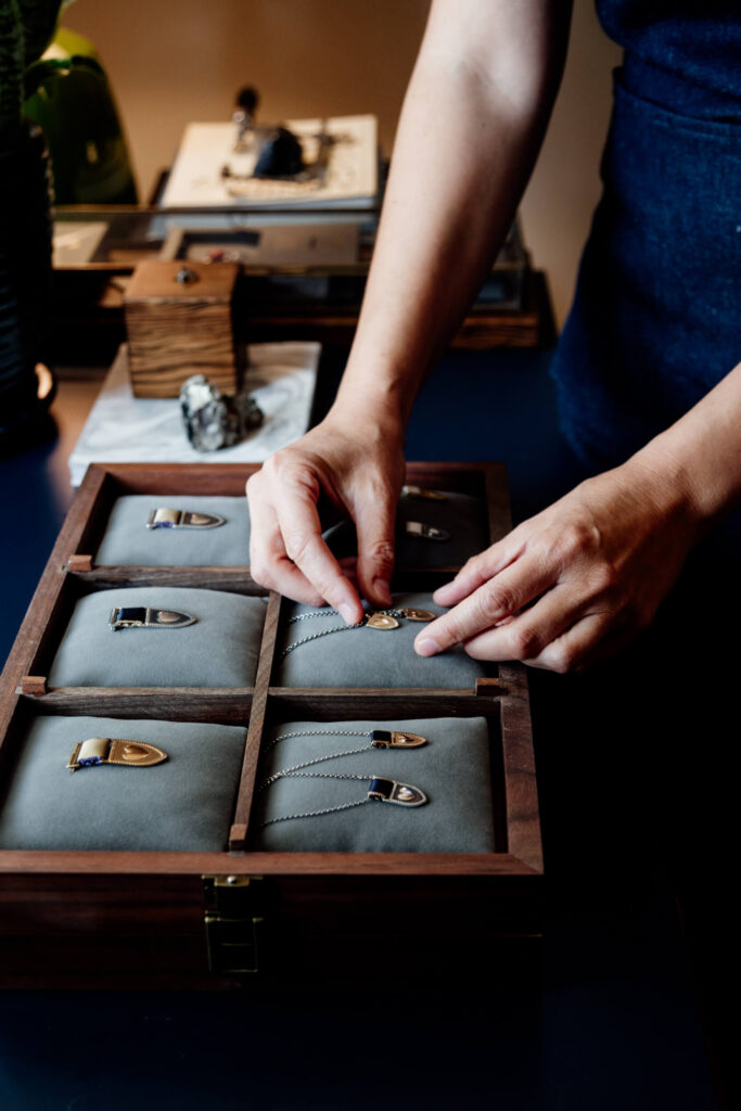 A pair of hands arranges some metal jewellery in a satin box.