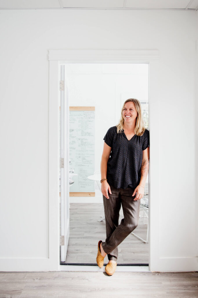 a woman leans against a door frame and smiles.