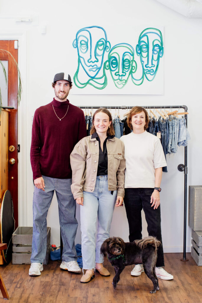 Three people smiling at the camera in front of their clothing racks in a consignment shop in Victoria, BC.