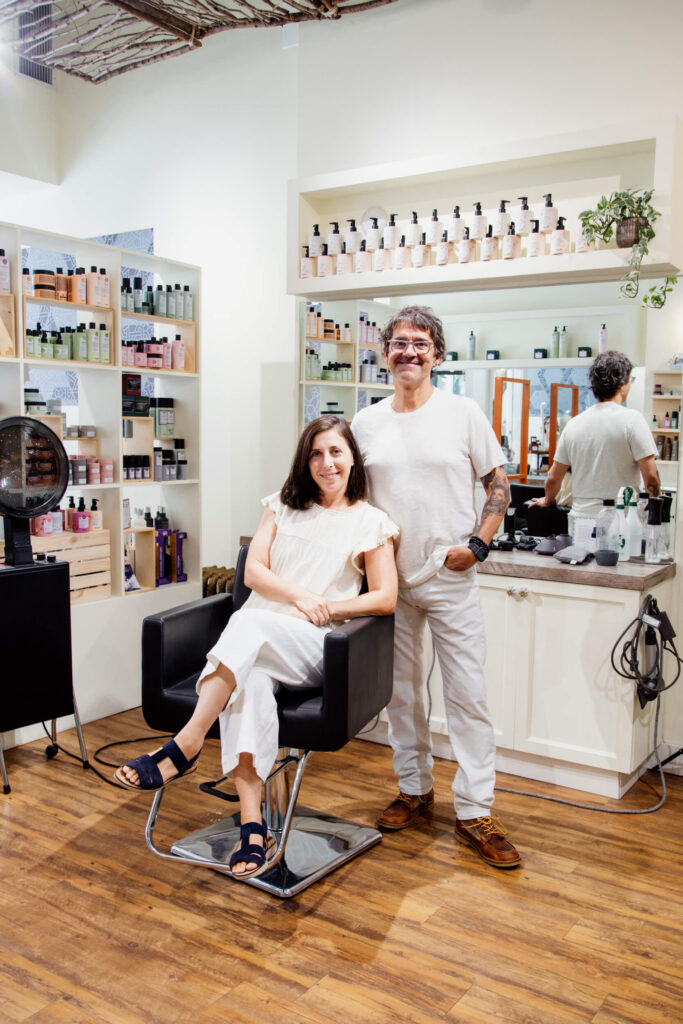 A woman in a hair salon sits in chair with a hairdresser standing beside her.