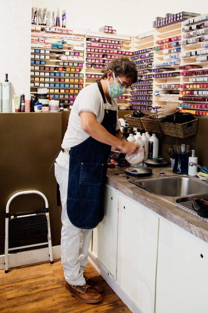 A hairdresser wearing a mask mixes hair colour over a sink.