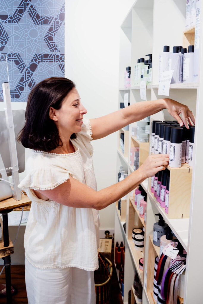 A woman tidies products on the shelf in her shop.