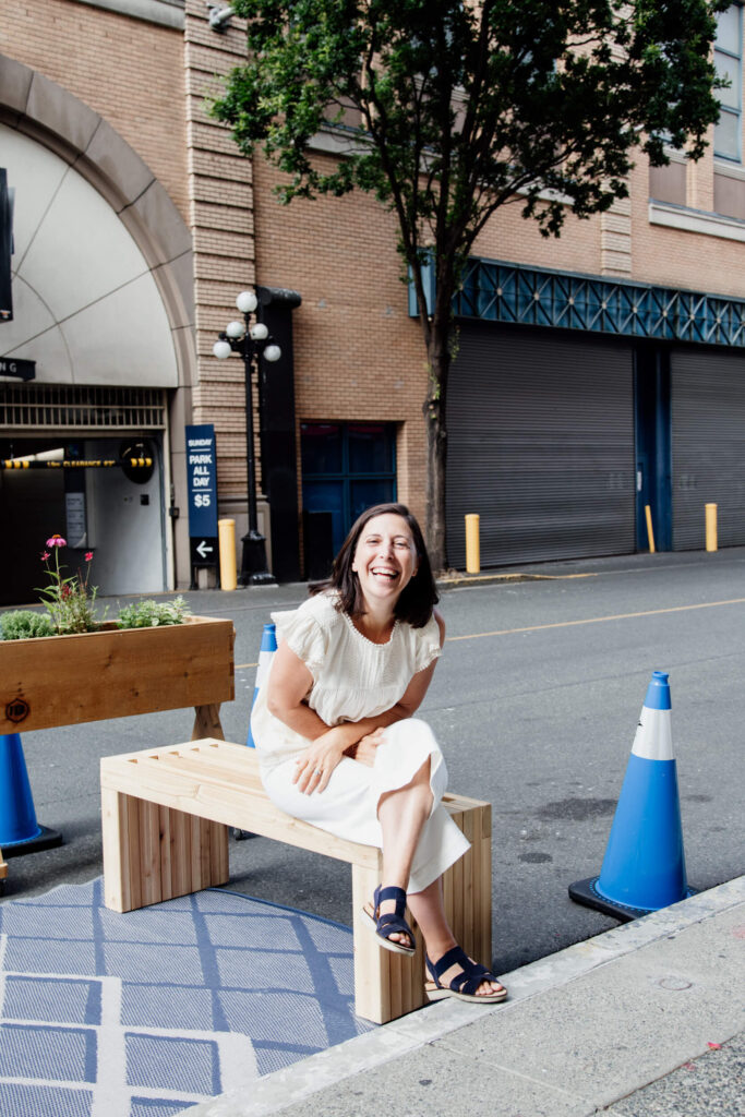 A woman sits on a bench and laughs.