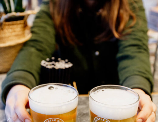 Nina, co-owner of Whistle Buoy Brewing in Victoria, BC, serves up two glasses of beer.