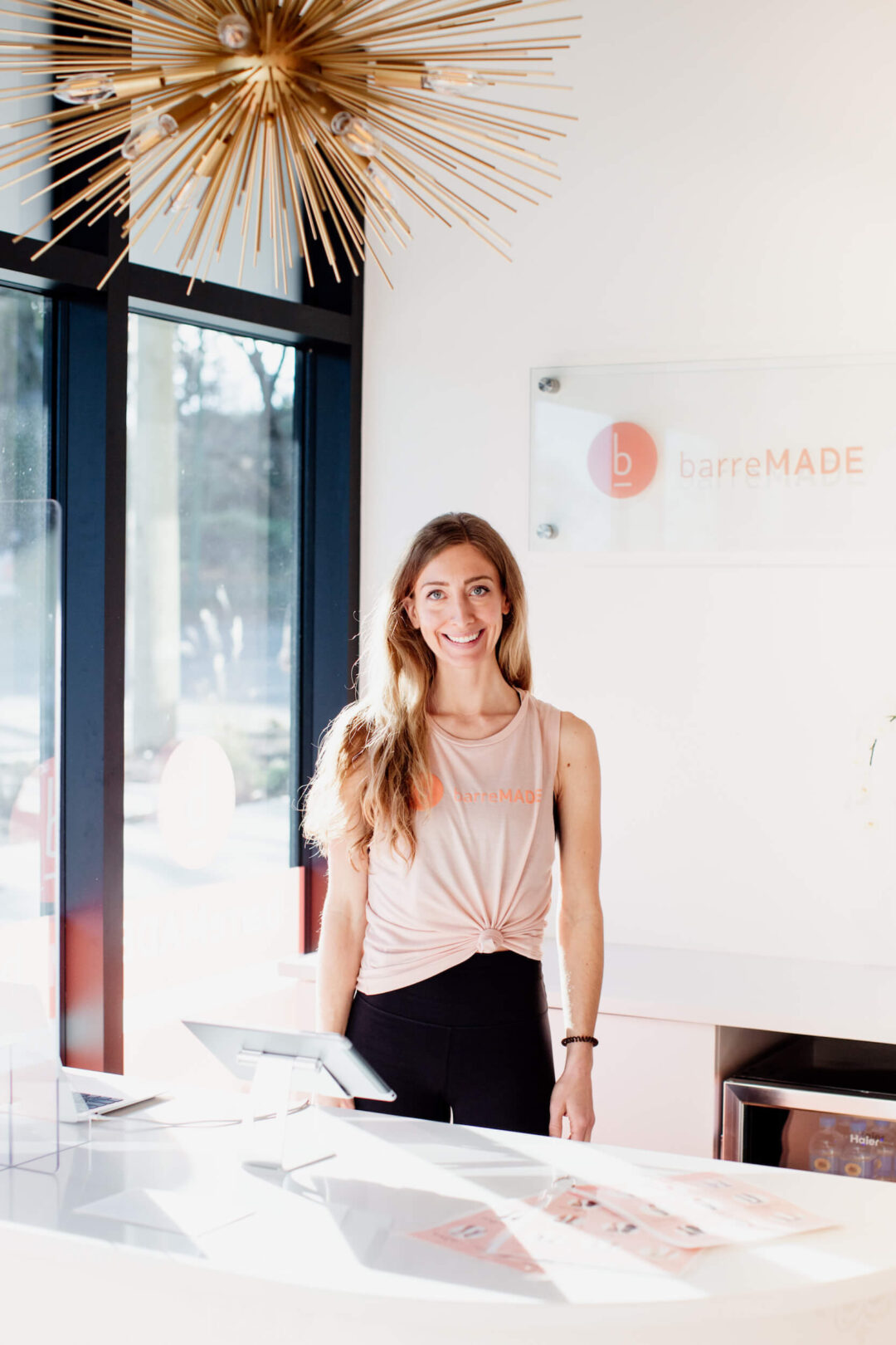 The owner of a barre studio stands and smiles at her desk in Victoria, BC.