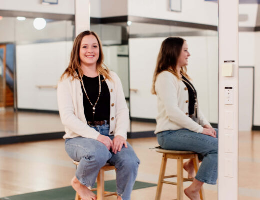 A woman sits on a stool in her yoga studio